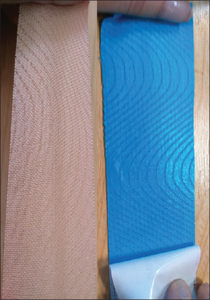 dd53907205a Figure 1: Distinctive appearance of blue- and beige-colored kinesiology  tapes. Figure showing woven polymer elastic strands when removed from the  paper ...